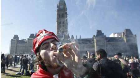Cannabis users celebrating the news with a joint outside Parliament Hill. Image stolen from the BBC.